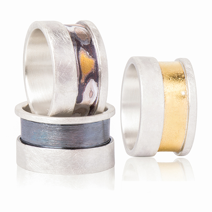 Rings in sterling silver, mat and tarnished, 22 carats gold or mokume gane, width 1,3 cm