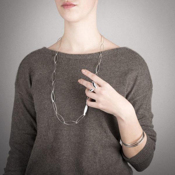 Bracelets fins portés en argent RJC, dans leurs deux versions: mat ou oxydé (anthracite), et également le sautoir et la bague (entre deux doigts) de la même collection. Vendu à l'unité.