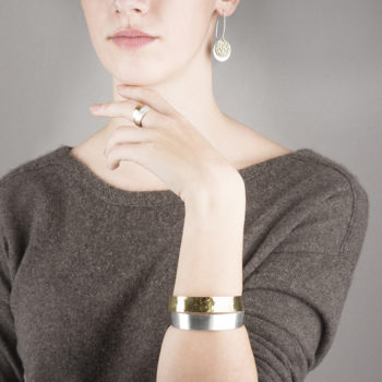 Earrings, ring and bracelet of the DOTS collection. In sterling silver and 22 ct gold.