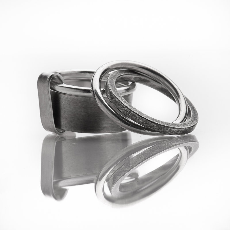 Double-bagues en argent, mat et oxydé. Grand modèle avec un anneau fil rond et une bague plate, et petit modèle avec deux anneaux (fil rond et carré)